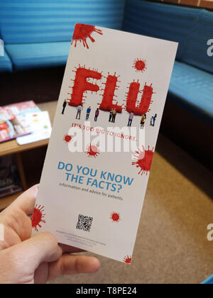 A leaflet with advice for patients about Flu is seen in an NHS local doctors surgery waiting room in Warwickshire, UK, On May 14, 2019. - Stock Photo