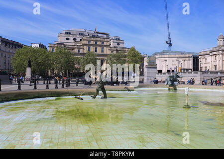 London, UK. 14th May 2019. Clean Up staff sweeps away the green residue which has accumulated at the bottom of the iconic Trafalgar Square fountains which has been emptied of water  in a major clean up.  Credit: amer ghazzal/Alamy Live News - Stock Photo