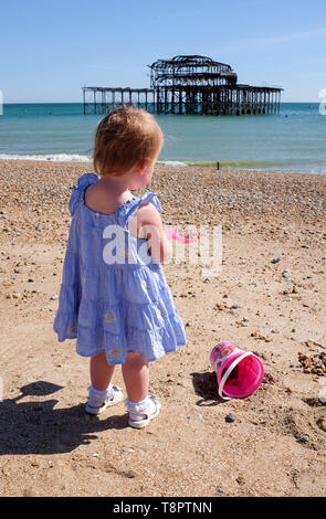 Brighton, UK. 14th May, 2019. A young 2 year old girl enjoys herself building sandcastles on Brighton beach on a hot sunny day with warmer weather forecast for the next couple of days throughout Britain . Credit: Simon Dack/Alamy Live News - Stock Photo