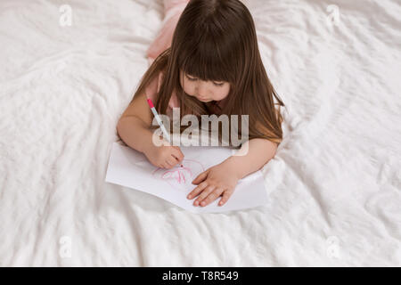 cute little girl drawing pictures while lying on bed. Kid painting at home. top view