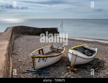 Fishing boats pulled up onto the shore beside a sea wall at Sidmouth, Devon, UK - Stock Photo