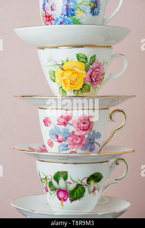 A stack of tea cups against a pink wall. - Stock Photo