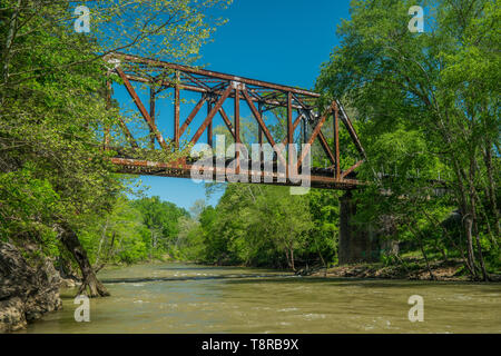 Old rusty train trestle over a fast flowing river - Stock Photo