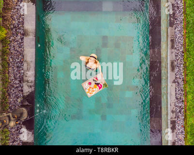Breakfast tray in swimming pool, floating breakfast in luxury hotel. Girl relaxing in the pool drinking smoothies and eating fruit plate, smoothie
