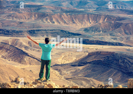 A man with hands in the air standing on the cliff in the desert - Stock Photo