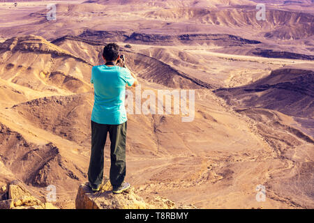 A man standing on the edge of the cliff in the desert and taking a photo - Stock Photo