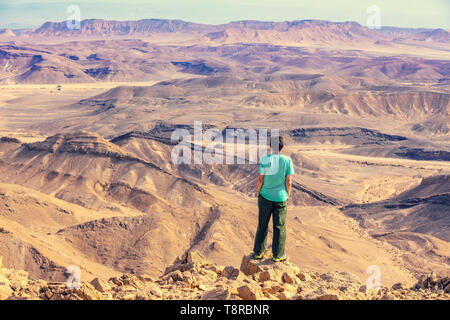 A man stands on the edge of a cliff in the desert and looks at a beautiful view. - Stock Photo