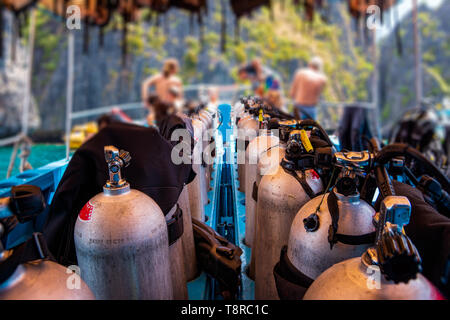 Scuba divers getting ready for diving on a boat full of equipment, Thailand - Stock Photo