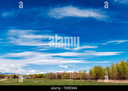 Beautiful blue sky with cirrus clouds; snow capped Rocky Mountains on horizon; Vandaveer Ranch; Salida; Colorado; USA - Stock Photo