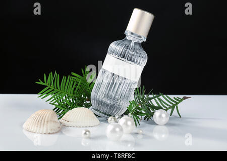 Bottle of perfume, sea shells and pearls on table against black background - Stock Photo