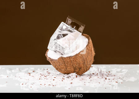 Bottle of perfume with fresh coconut on table against black background - Stock Photo