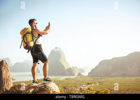 Backpacker tourist stands on big rock and takes mobile photo at viewpoint - Stock Photo