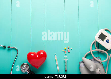 Top view of stethoscopes, Plastic red heart, Automatic portable blood pressure or heart rate monitor and drugs on green wooden desk, clinic work desk  - Stock Photo