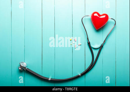 Top view of stethoscopes, red heart model and drugs on green wooden desk, clinic working desk, medical and healthy concept. - Stock Photo