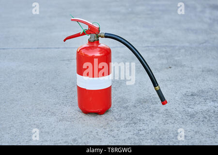 A single isolated fire extinguisher on concrete in safety red with a white tape strip around the middle. - Stock Photo