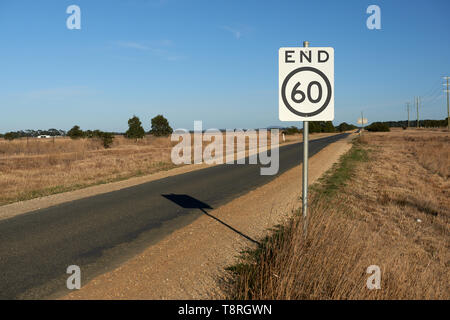 End of speed restriction road sign on a narrow Australian country road signifying an end to a 60 kilometre per hour safety speed limit area. - Stock Photo