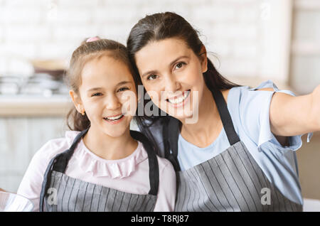 Cute Little Girl And Her Mom In Aprons Making Selfie - Stock Photo