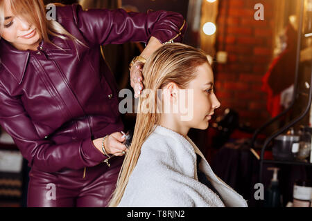 Hairdresser brushing wet hair of beautiful young blond woman in beauty salon after washing hair. Hair health, beauty salon,spa concept.