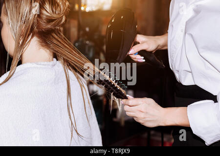Hairdresser drying blond female hair with professional hairdryer in beauty salon. Closeup of hairstylist using hairbrush and hair dryer. - Stock Photo