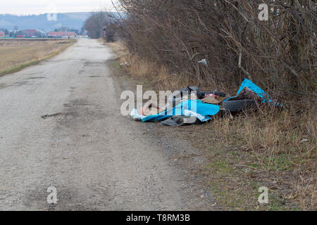 Fly tipped rubbish dumped in a lay-by in a country lane. Heap of illegally dumped household rubbish left on a side of the cart-road. Roadside fly tipp - Stock Photo