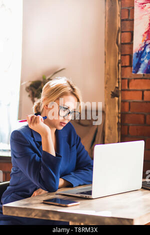 Young attractive caucasian female blogger typing new post during sitting at cafe with laptop and smart phone on the table. Beautiful blonde business w