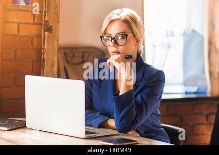 Indoor shot of caucasian thoughtful female in glasses sitting at the table touching face with pen while thinking about new project, checking documents - Stock Photo