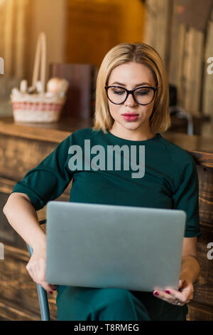 Confident female freelancer sitting on chair holding laptop looking with serious and thoughtful expression. Young businesswoman in glasses using PC fo - Stock Photo