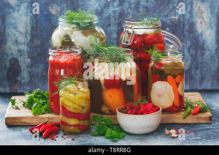 Colorful preserved and marinated seasonal vegetables with herbs on rustic wooden kitchen table - Stock Photo
