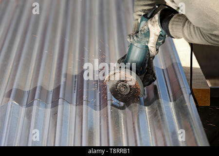 A man cutting steel plate with an angle grinder - Stock Photo