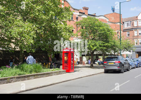 A converted Sir Giles Gilbert Scott K6 phone box, now used to store a defibrillator, in front of the Olympic Cinema, Church, Barnes, London, SW13, UK - Stock Photo