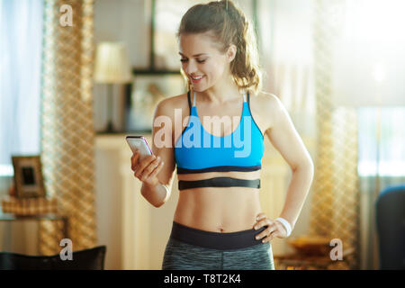 smiling young sports woman in fitness clothes in the modern living room wearing heart rate monitor using smartphone to track heart rate in fitness app - Stock Photo