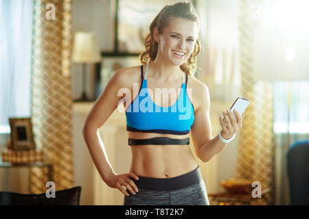 smiling fit woman in fitness clothes in the modern living room wearing heart rate monitor using smartphone to track heart rate in fitness app. - Stock Photo