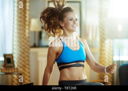 smiling young sports woman in fitness clothes in the modern house workout and using heart rate monitor. - Stock Photo