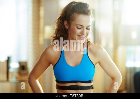 smiling fit sports woman in fitness clothes with heart rate monitor in the modern living room. - Stock Photo