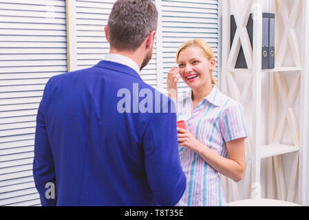 Two of attractive business people, standing next to each other, holding a cups, smiling standing at office. Smiling business couple at office room talking in coffee break. Meeting coffee - Stock Photo