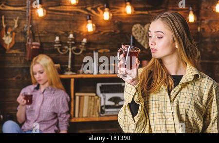 Friends on relaxed faces in plaid clothes relaxing, defocused. Friends enjoy mulled wine in warm atmosphere, wooden interior. Girls relaxing and drinking mulled wine. Rest and relax concept. - Stock Photo