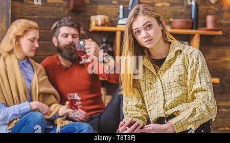 Blond girl with big eyes in yellow vintage shirt sitting in living room of countryside wooden cottage. Bearded man and his wife chatting, drinking and having fun while their daughter sits alone. - Stock Photo