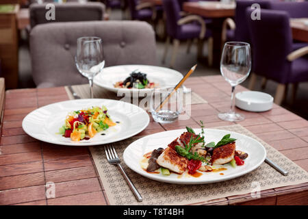 Fish fillet with vegetables and another food on restaurant table - Stock Photo
