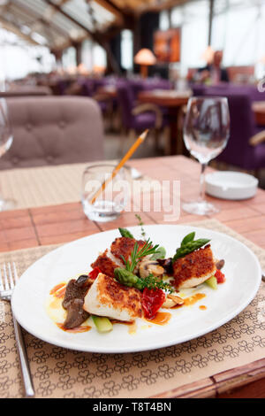 Fish fillet with mushrooms and asparagus on restaurant table - Stock Photo