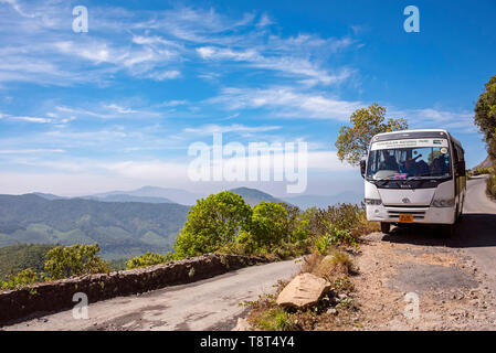 Horizontal view of a coach transporting people around Eravikulam National Park in Munnar, India. - Stock Photo