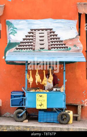 A Mexican food vendor sells fresh chickens under a mural of the El Tajin pyramid outside the central Market in Papantla, Veracruz, Mexico. - Stock Photo