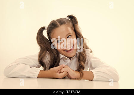 Perfect schoolgirl with tidy fancy hair. School hairstyle ultimate top list. Prepare kid first school day. Schoolgirl happy carefree face cute ponytail. Excellent pupil lean on desk isolated white. - Stock Photo