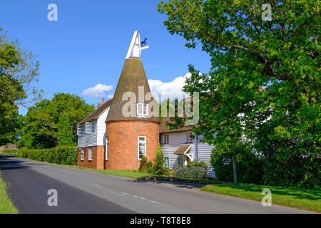 Picturesque roadside Kentish Oast House, now converted to a house, near Pluckley, Kent, UK. A traditional Kentish countryside scene. - Stock Photo