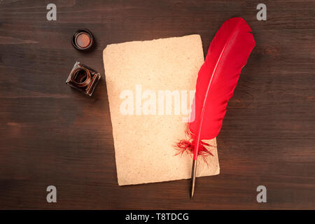 A vintage background with a quill pen on a piece of old parchment paper, with an ink well, shot from above on a dark wooden background - Stock Photo
