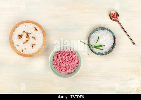 Gourmet spices. An overhead photo of various types of finishing salt and pepper, shot from the top on a white wooden background with a place for text - Stock Photo