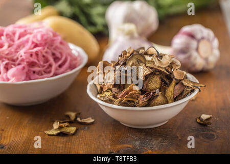 Dried mushrooms sour cabbage garlic and potatoes on wooden table - Stock Photo