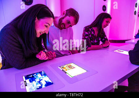 People playing VR games and ordering drinks on iPads embedded in the tables at Otherworld Virtual Reality Arcade and Bar, London, UK - Stock Photo