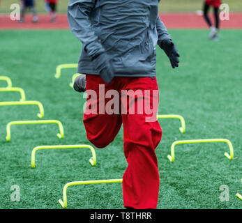 A high school runner is sprinting over yellow mini hurdles on a green turf field on a cold day in December. - Stock Photo