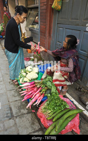 Women selling and buying produce in market behind Durbar Square, Kathmandu, Nepal - Stock Photo