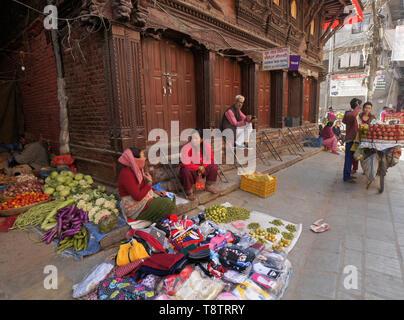 Vendors selling clothing and produce in street market near Durbar Square, Kathmandu, Nepal - Stock Photo
